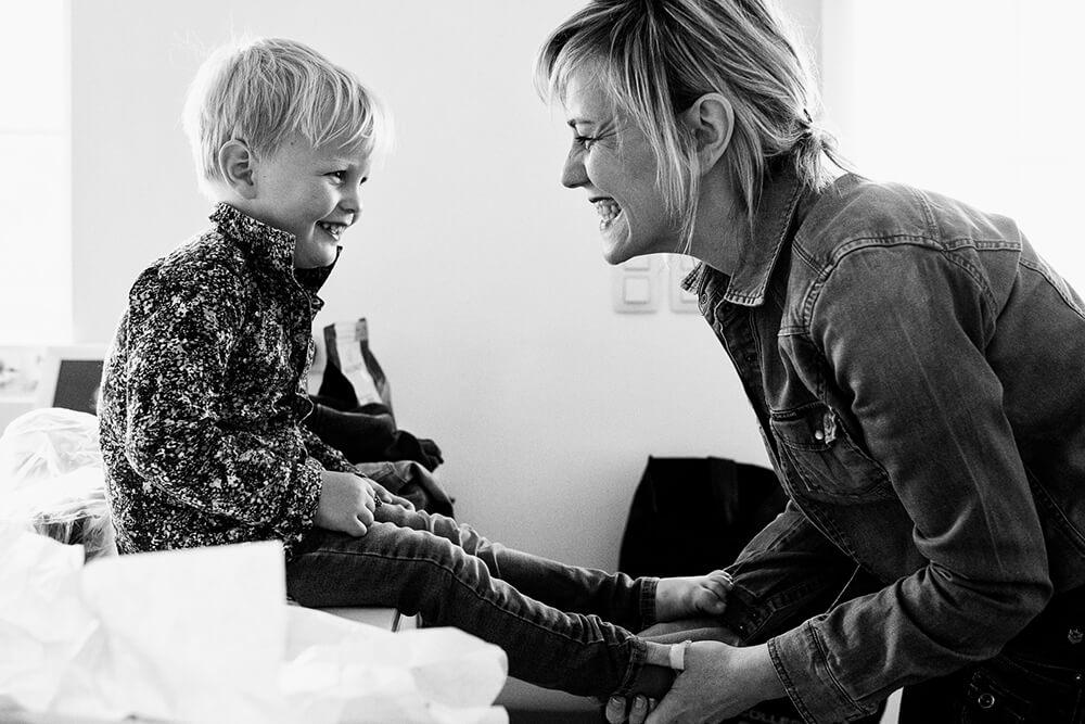 foto mama en zoon lachen naar elkaar. familiereportage op locatie